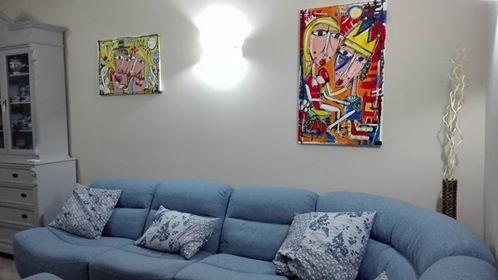 salotto con divano celeste con i dipinti arte moderna alessandro siviglia pop art soggiorno quadri moderni studio legale arredamento quadri a olio